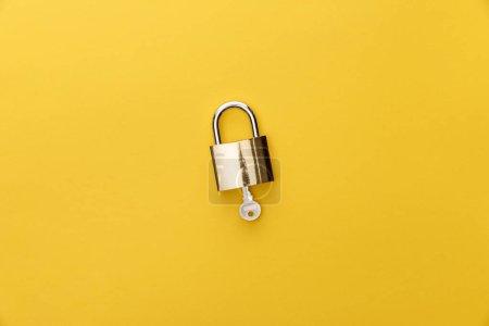 Photo pour Vue supérieure de la clef dans le cadenas sur le fond jaune - image libre de droit