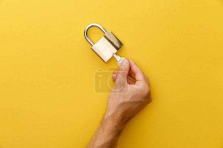 Photo for Cropped view of man holding key in padlock on yellow background - Royalty Free Image