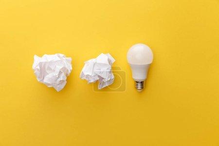 Photo pour Vue du dessus du papier froissé près de l'ampoule sur fond jaune - image libre de droit