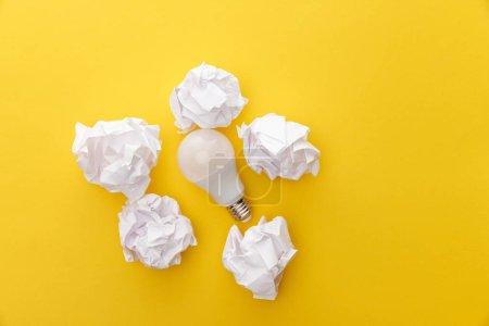 Photo pour Vue de dessus de l'ampoule entre le papier froissé sur fond jaune - image libre de droit
