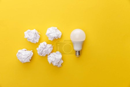 Photo for Top view of light bulb near crumpled paper on yellow background - Royalty Free Image