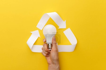 Photo for Cropped view of woman holding light bulb under paper craft triangle on yellow background - Royalty Free Image