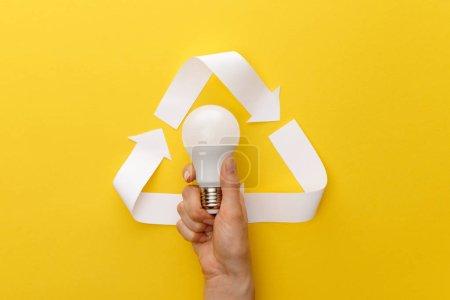 Photo pour Vue recadrée de femme retenant l'ampoule sous le triangle d'artisanat de papier sur le fond jaune - image libre de droit