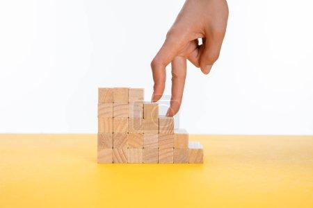 Photo pour Vue recadrée de la femme marchant avec les doigts sur des marches en bois sur une surface jaune isolée sur blanc - image libre de droit