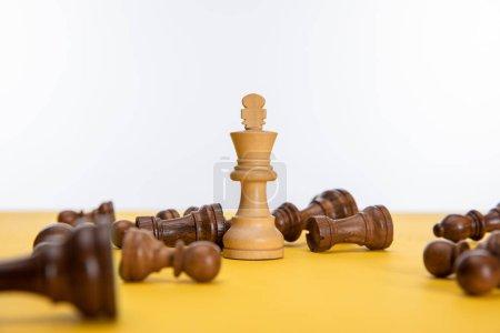 Photo pour Roi des échecs près d'autres figures sur la surface jaune isolé sur blanc - image libre de droit