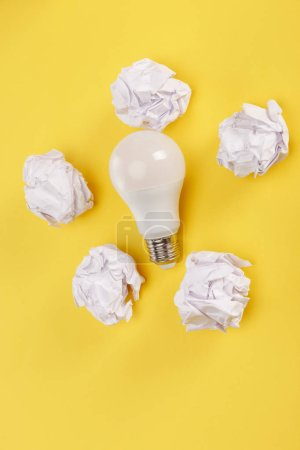 top view of crumpled paper around light bulb on yellow background