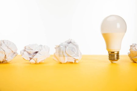 Photo for Crumpled paper near light bulb on yellow surface isolated on white - Royalty Free Image