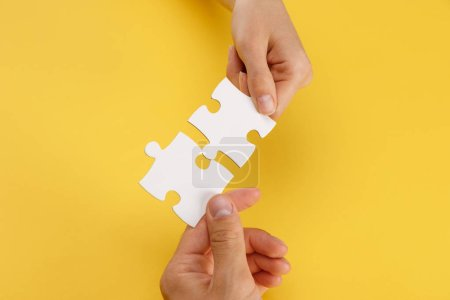Foto de Cropped view of woman and man matching pieces of white puzzle on yellow background - Imagen libre de derechos