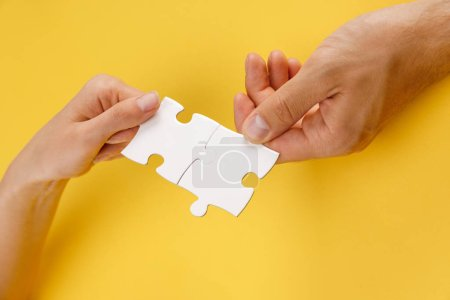 cropped view of man and woman matching pieces of white puzzle on yellow background
