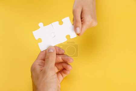 Foto de Cropped view of man and woman holding pieces of white puzzle on yellow background - Imagen libre de derechos