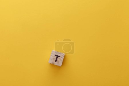 Photo for Top view of wooden cube with t letter on yellow background - Royalty Free Image