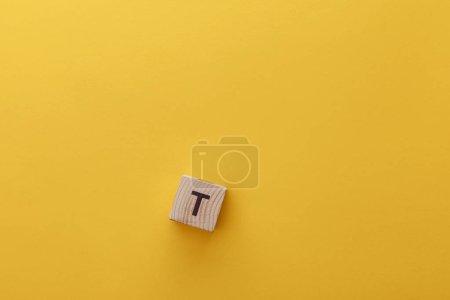 Photo pour Vue du dessus du cube en bois avec lettre t sur fond jaune - image libre de droit