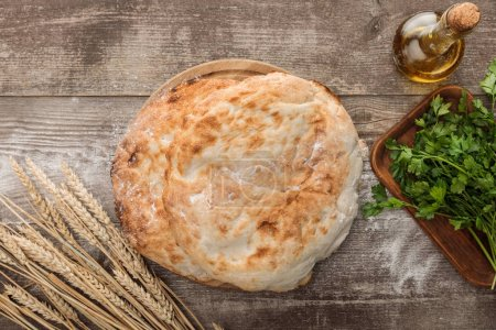 Photo for Top view of lavash bread near wheat spikes, fresh parsley and olive oil on wooden table - Royalty Free Image