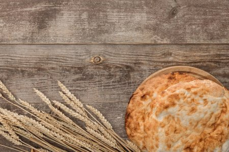 Photo for Top view of lavash bread near wheat spikes on wooden table - Royalty Free Image