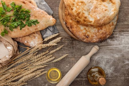 Photo for Top view of lavash bread on gray towel near flour package, wheat spikes, fresh greenery and olive oil on wooden table - Royalty Free Image
