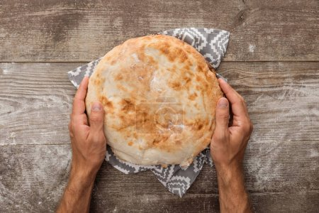 Photo for Cropped view of man holding lavash bread on gray towel with pattern on wooden table - Royalty Free Image