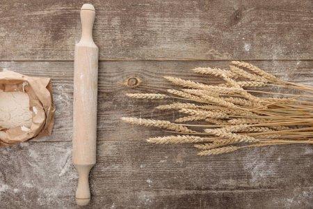 Photo pour Vue supérieure des pointes de blé, du rouleau à pâtisserie et du paquet de farine sur la table en bois - image libre de droit