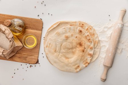 Photo for Top view of flat lavash bread near rolling pin and wooden cutting board with flour and olive oil on white surface with peppercorns - Royalty Free Image