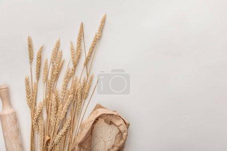 Photo pour Vue de dessus des épis de blé, rouleau à pâtisserie et paquet de farine isolé sur blanc - image libre de droit