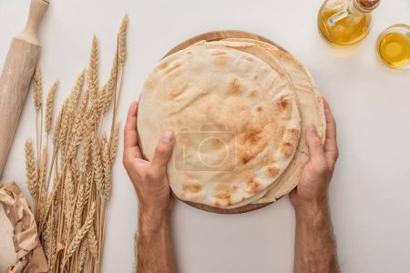 Photo for Cropped view of man holding flat lavash bread near wheat spikes, rolling pin and olive oil on white surface - Royalty Free Image