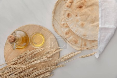 Photo for Top view of flat lavash bread with white towel near cutting board with spikes and oil on marble surface - Royalty Free Image