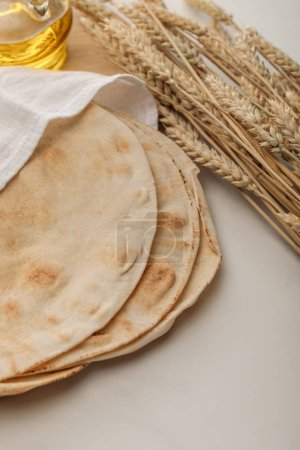 Photo for Lavash bread covered with towel near wheat spikes and oil on white surface - Royalty Free Image