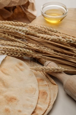 Photo for Lavash bread near rolling pin and cutting board with spikes and oil - Royalty Free Image