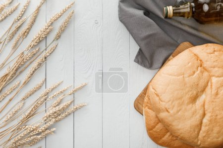 Photo for Top view of lavash bread on towel near spikes and oil on white wooden surface - Royalty Free Image