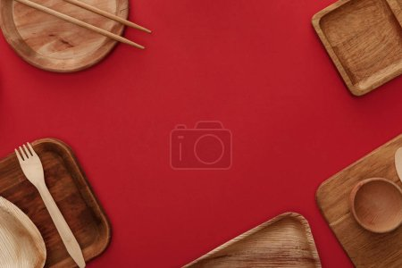 top view of wooden dishes, cup, fork and chopsticks on red background
