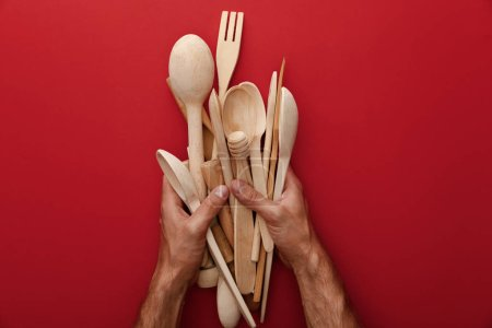 Photo for Cropped view of man holding wooden spoons, fork and kitchenware on red background - Royalty Free Image
