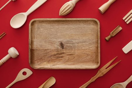 top view of natural rectangular  wooden dish on red background with kitchenware