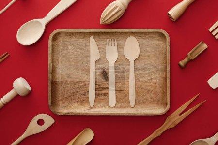 Foto de Vista superior del plato de madera rectangular natural con cubertería sobre fondo rojo con menaje de cocina - Imagen libre de derechos