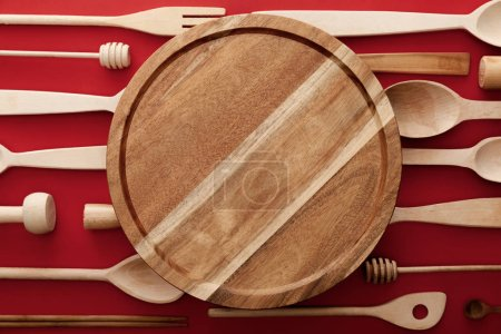 Photo for Top view of round wooden cutting board on red background with kitchenware - Royalty Free Image