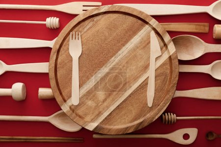 Photo for Top view of round wooden cutting board with knife and fork on red background with kitchenware - Royalty Free Image
