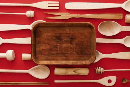 Photo for Top view of empty rectangular wooden dish on red background with kitchenware - Royalty Free Image