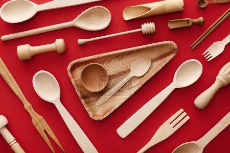 Foto de Vista superior del plato de madera triangular con taza y cuchara sobre fondo rojo con utensilios de cocina - Imagen libre de derechos