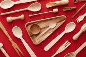 """Постер, картина, фотообои """"верхний вид треугольника деревянное блюдо с чашкой и ложкой на красном фоне с кухонной посудой"""""""