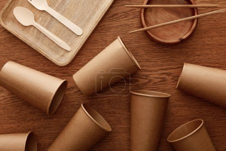 Photo for Top view of wooden dishes, cutlery, chopsticks and paper cups on brown background - Royalty Free Image