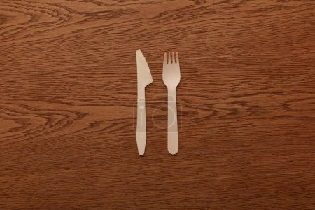 Photo for Top view of wooden fork and knife on brown background - Royalty Free Image