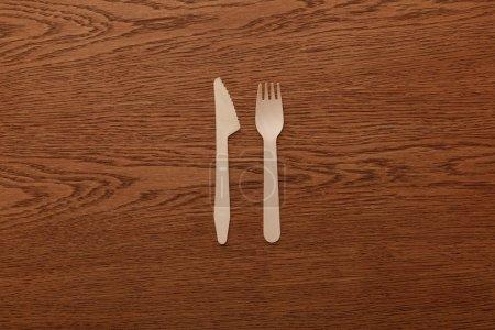 Photo pour Vue supérieure de la fourchette et du couteau en bois sur le fond brun - image libre de droit