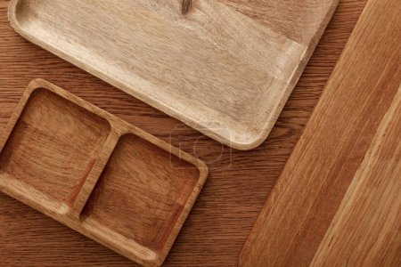 top view of wooden dishes and cutting board on brown background