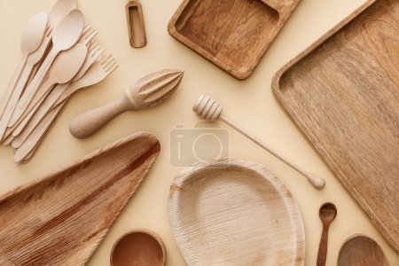 Photo for Top view of wooden plates, dishes, forks, spoons and hand juicer on beige background - Royalty Free Image