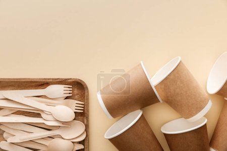 Photo for Top view of rectangular wooden dish with forks and spoons near paper cups on beige background - Royalty Free Image