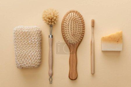 Photo pour Vue de dessus de l'éponge de bain naturelle près de brosse à dents, brosse à cheveux, brosse à corps et savon sur fond beige - image libre de droit
