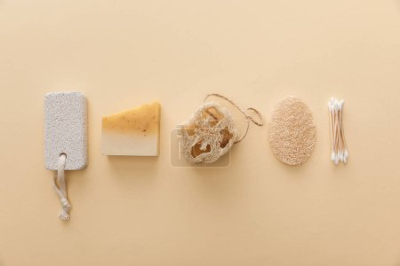 Photo for Top view of natural soap near cotton swabs, loofah and pumice stone on beige background - Royalty Free Image