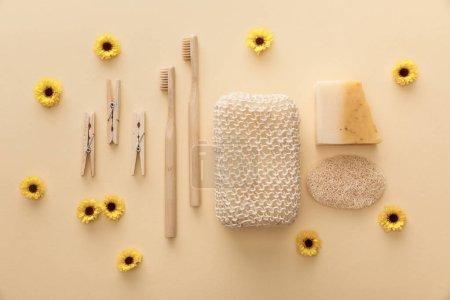 Photo pour Vue supérieure des pinces à linge en bois, brosses à dents, éponge de bain, savon naturel et loofah sur le fond beige avec des fleurs - image libre de droit