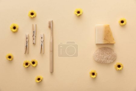 Photo for Top view of wooden clothespins, toothbrush, natural soap and loofah on beige background with flowers - Royalty Free Image