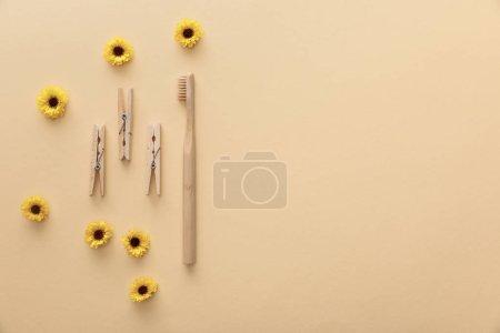 Photo pour Vue de dessus des pinces à linge et brosse à dents en bois sur fond beige avec des fleurs - image libre de droit