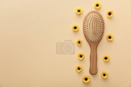 Photo for Top view of wooden hairbrush on beige background with flowers - Royalty Free Image