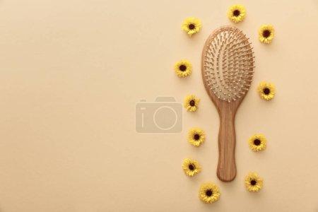 Photo pour Vue supérieure de brosse à cheveux en bois sur le fond beige avec des fleurs - image libre de droit